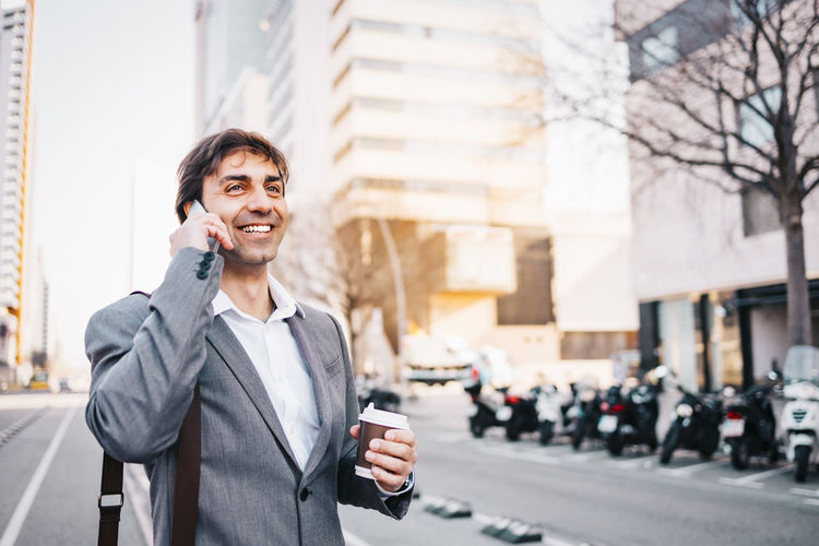 Businessman talking on phone while standing on road