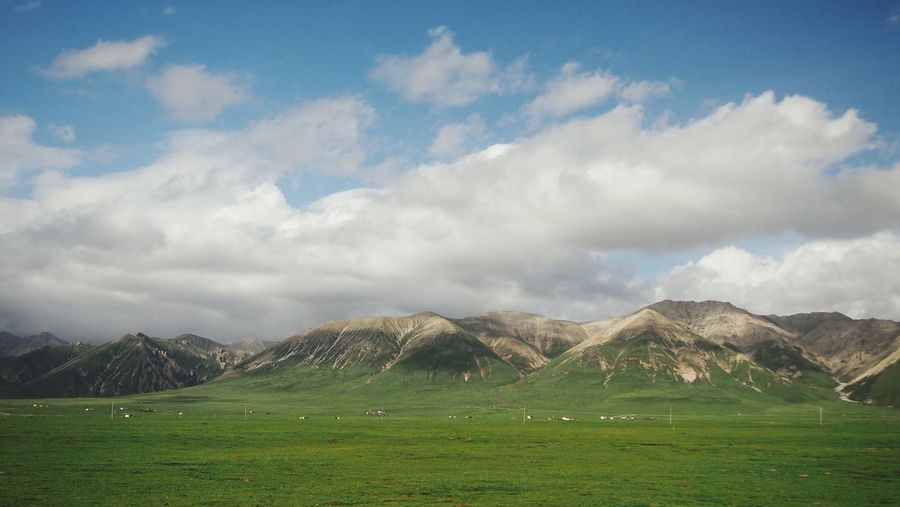 Scenic view of grassy field and mountain range against cloudy sky