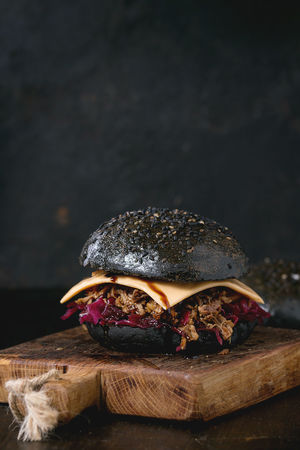 Black burger with beef stews, cheese, red cabbage and balsamic sauce served on small wooden chopping board over wooden table with black background. Black Background Burger Dark Fast Food Food And Drink Homemade Food Pork Stew Black Burger Black Food Cabbage Cheese Chopping Board Hamburger Junk Food Meat Modern Food Purple Sauce