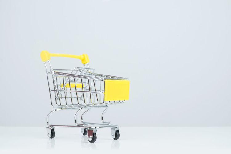 Side view of shopping cart on white Background. Background Basket Business Buy Commerce Consumer Consumerism Customer  E-commerce Empty Equipment Grocery Handle Industry Isolated Luggage Cart  Mall Mall Cart Market Metal Mini Modern Object Price Purchase Push Cart Retail  Sale Shop Shopping Cart Single Single Object Small Store Super Mart Supermarket Trolley Wheel Wheels White White Background Yellow