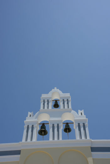 close up of a built structure of a church with three bells Architecture Built Structure Building Exterior No People Low Angle View White Color High Section Outdoors Spirituality Religion Belief Place Of Worship Clear Sky Sky Tower Bell Santorini, Greece Building Day Church Orthodox Church Greece