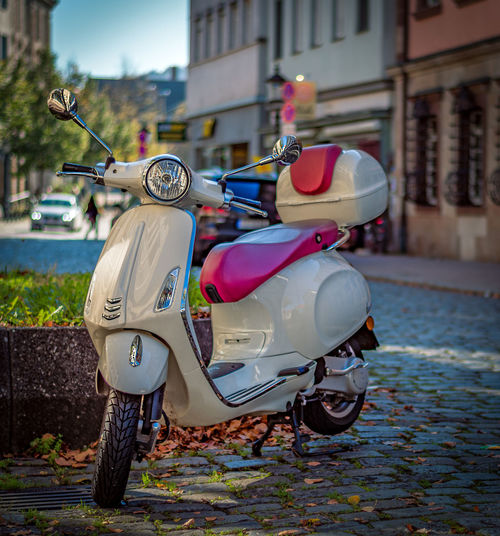 Motor scooter parked on street against buildings