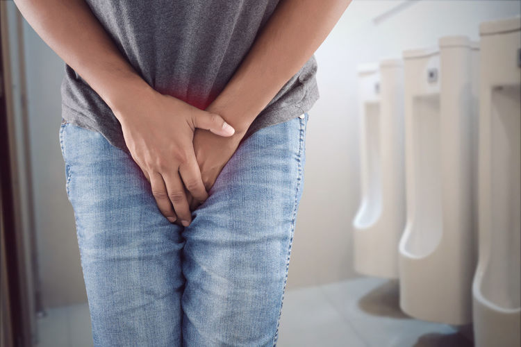 Midsection of man suffering from urinal pain in bathroom