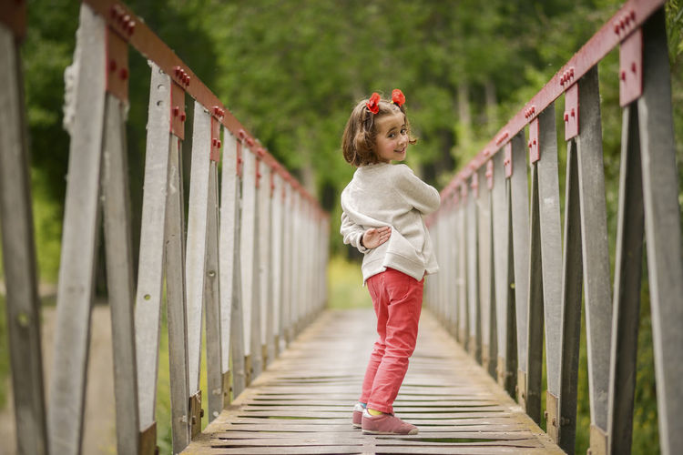 Cute little girl with four years old having fun in a rural bridge Full Length One Person Childhood Child Wood - Material Railing Casual Clothing Standing Real People Girls Females Side View Day Lifestyles Fence Plant Bridge Hairstyle Footbridge Innocence