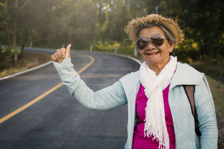 Woman hitchhiking while standing on road