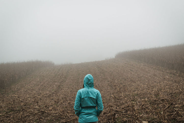 Rear view of woman wearing warm clothing standing on field during foggy weather