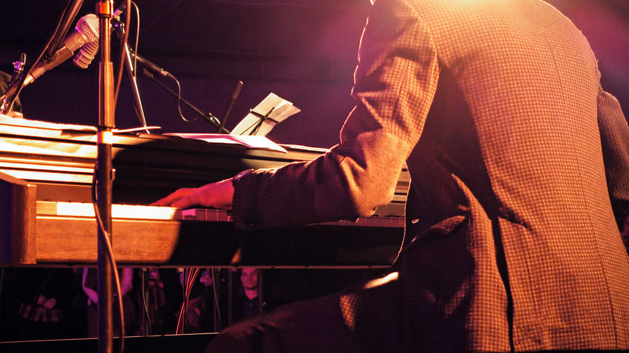 Midsection Of Man Playing Piano During Music Concert