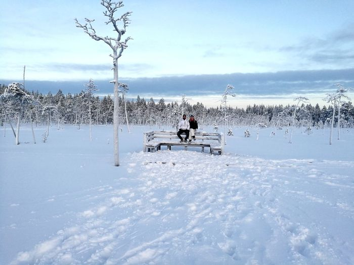 People Sitting On Bench Against Sky During Winter