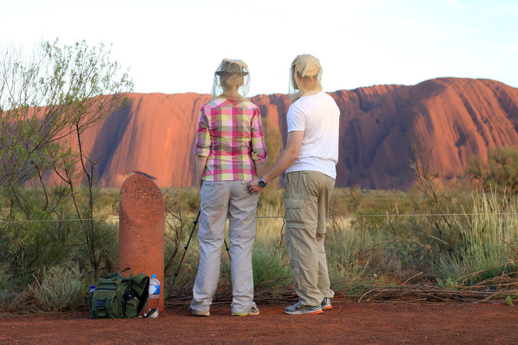 rear view of a couple wearing mosquito nets looking at the Uluru in Australia Australia Ayers Rock Connected By Travel Uluru Beauty In Nature Bonding Casual Clothing Friendship Hill Landmark Landscape Leisure Activity Lifestyles Mosquito Net Nature Outdoors Protection Real People Rear View Standing Togetherness Two People Watching
