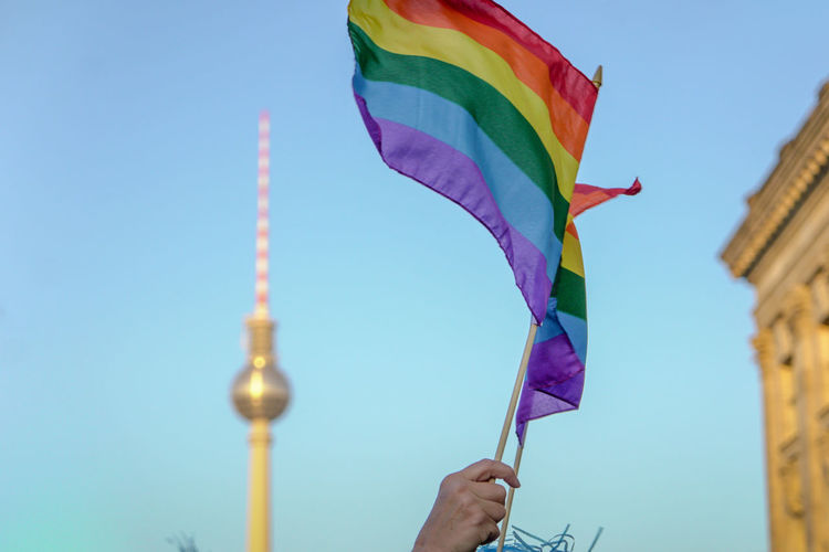 Low angle view of hand holding rainbow flag against sky