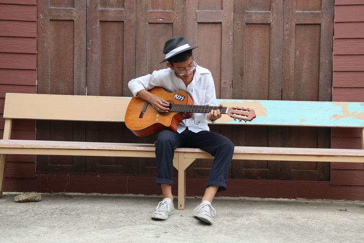 Full length of man playing guitar