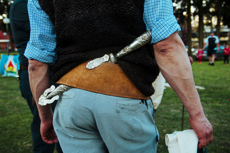 Midsection of man with dagger standing in park