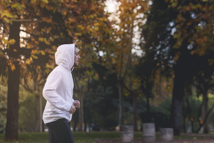 Young boy exercising in white sweatshirt. healthy lifestyle concept. outdoors shooting. side shot
