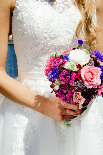 Midsection Of Woman Holding Flower Bouquet On Wedding Day