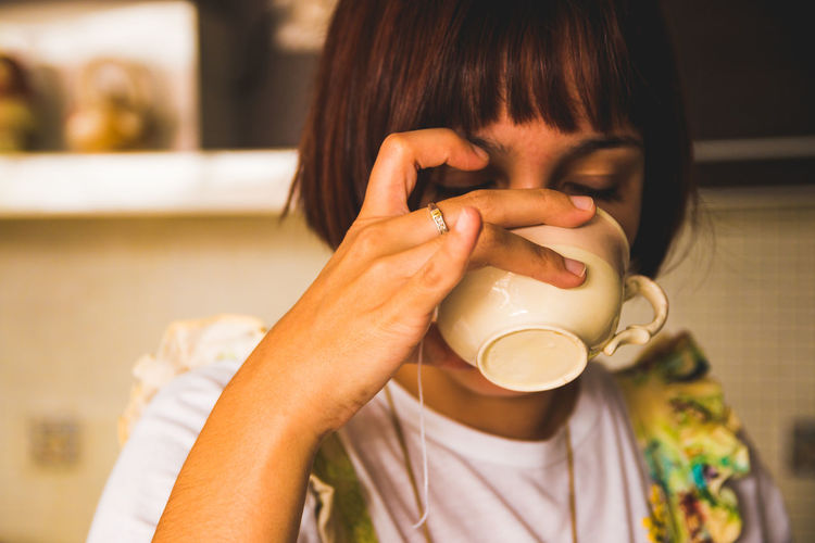 Close-up of woman drinking coffee in cup
