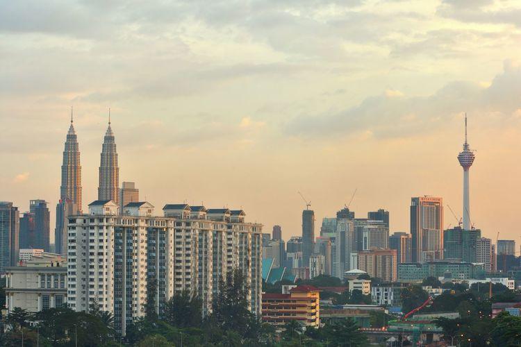 Menara kuala lumpur and petronas towers against sky in city
