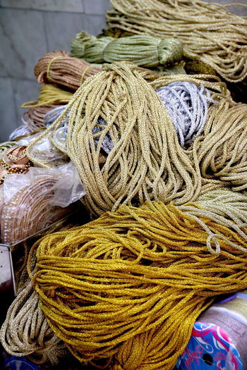 India Textile Industry Background Basket Close-up Commercial Fishing Net Complexity Day Focus On Foreground Golden Shimmer High Angle View Indoors  Jewelry Large Group Of Objects Material Design No People Rope Still Life String Structures & Lines Tangled Textile