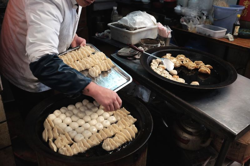 Chef Frying Jiaozi In Kitchen