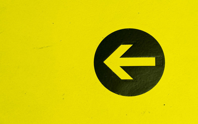 Close-up of arrow sign on yellow wall