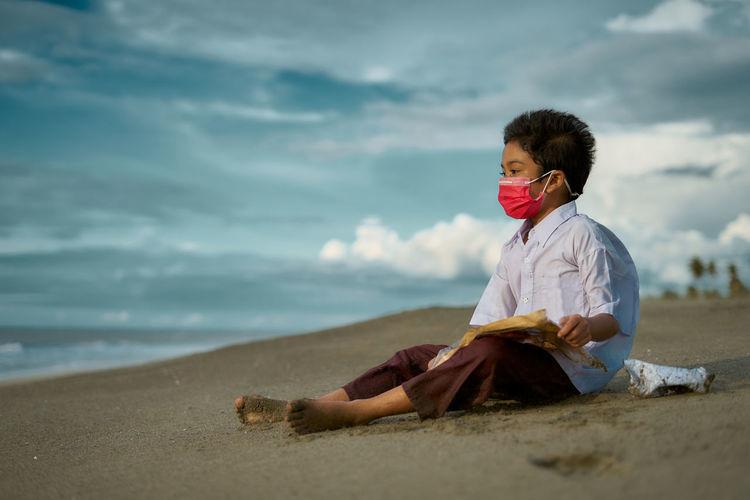 Boy wearing mask sitting at beach against sky