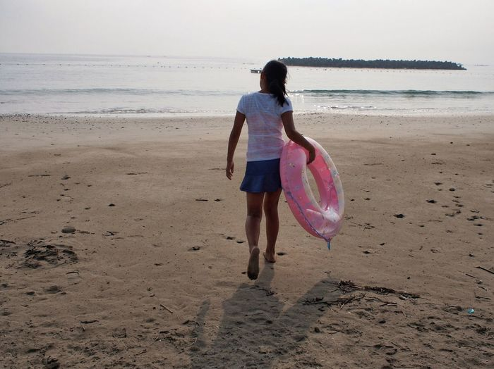 Rear view full length of girl walking with inflatable ring at beach