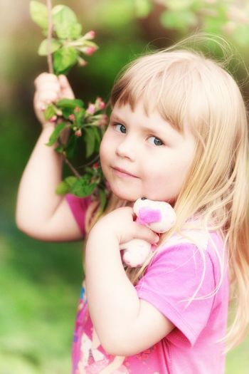 Portrait of cute girl playing with pink petals