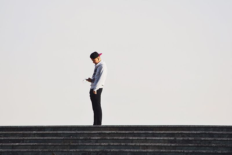 Young man using on mobile phone while standing on steps against clear sky