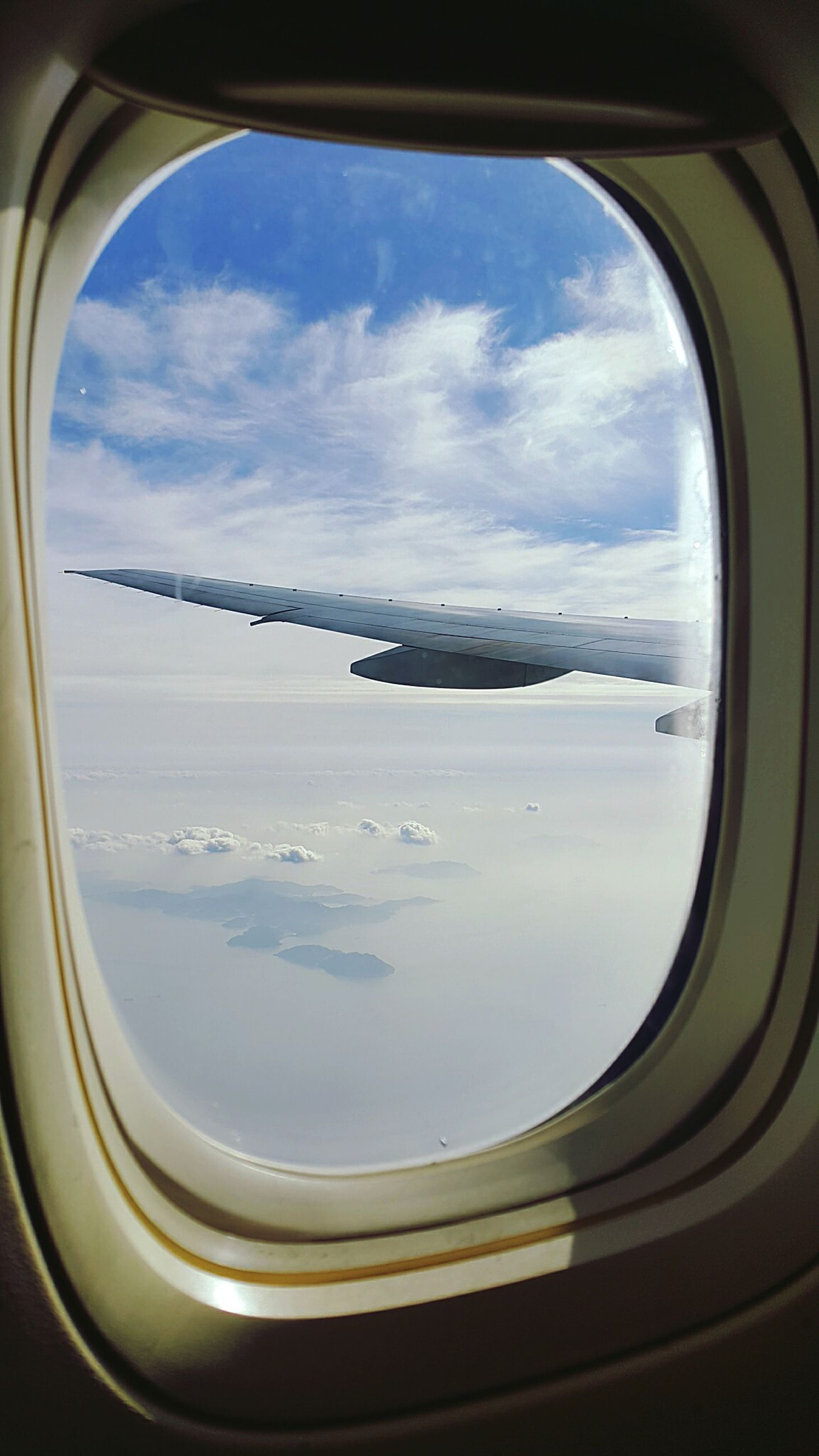window, vehicle interior, transportation, airplane, mode of transport, air vehicle, sky, transparent, glass - material, indoors, cloud - sky, flying, cloud, part of, looking through window, public transportation, travel, journey, cropped, day