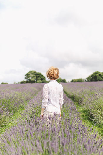 REAR VIEW OF WOMAN STANDING IN FIELD OF LAVENDER