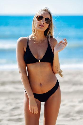 Portrait young bikini woman wearing sunglasses at beach