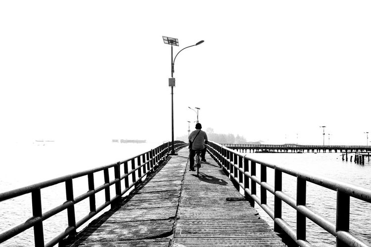 A man worker #wonderfulindonesia #blackandwhite #bnw #humaninterest #humanity #LeadingLines #kurmelihat Railing One Man Only Pier Outdoors Only Men One Person Adult People Bridge - Man Made Structure first eyeem photo