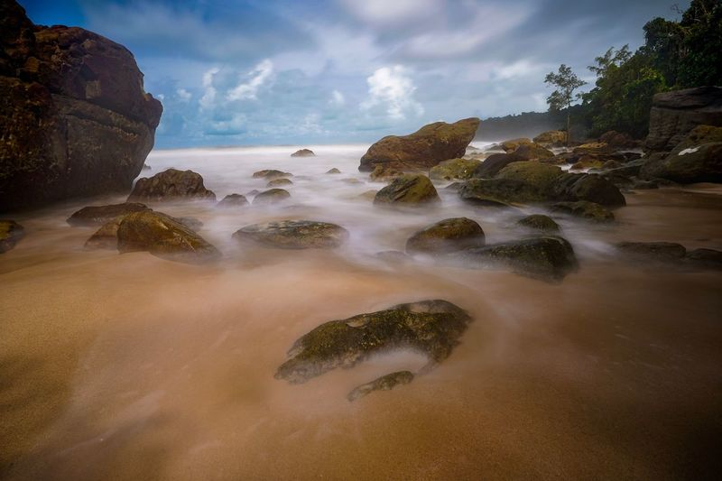 A scenic view of a long exposure shot at a stony beach in Kuching, Sarawak Water Sea Land Sky Cloud - Sky Beach Rock Solid Beauty In Nature Scenics - Nature Rock - Object Idyllic Nature Tranquility Tranquil Scene Sand No People Tree Motion