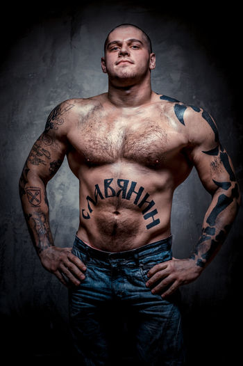 Portrait of shirtless muscular man with tattoos standing against gray background