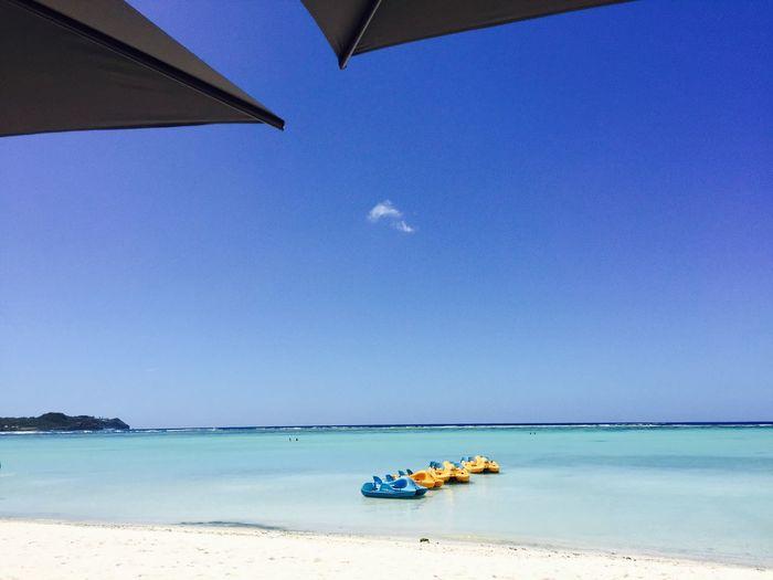 Boat on beach against clear blue sky