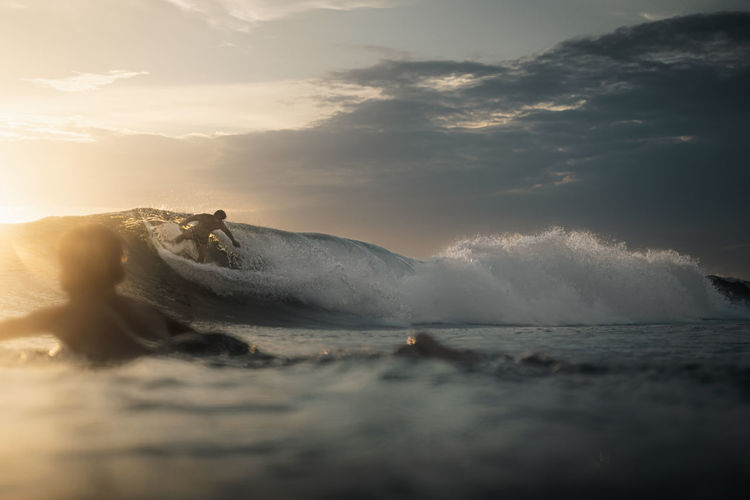 Cutting shiny green walls of water, surfphotography at golden hour