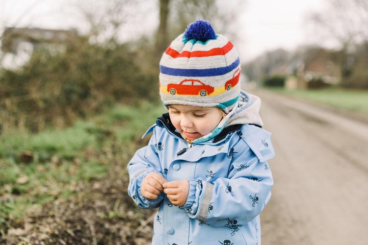 Boy wearing hat standing on field