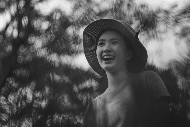 Low angle view of happy woman looking away against trees