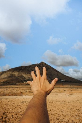 Cropped hand of man gesturing against mountain and sky