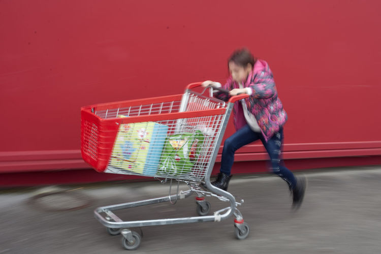 Cart Red Red Color Red Cart Shopping Cart One Person Full Length Blurred Motion Pushing Retail  Young Adult Motion Shopping Store Speed Transportation Consumerism Supermarket Customer  Groceries Riding Jeans Red Background Motion Blur Fun Streetwise Photography Analogue Sound