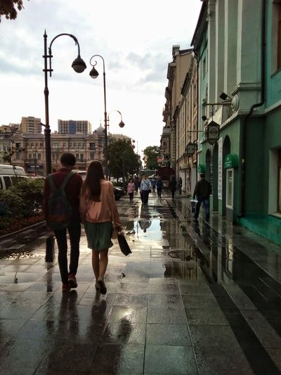 Street after the summer rain Wet Rain Rainy Day Summer City Water Street Sky Cloud - Sky People Walking Togetherness Young Adult Day Outdoors Lamp Posts Puddle Reflection Architecture Building Exterior