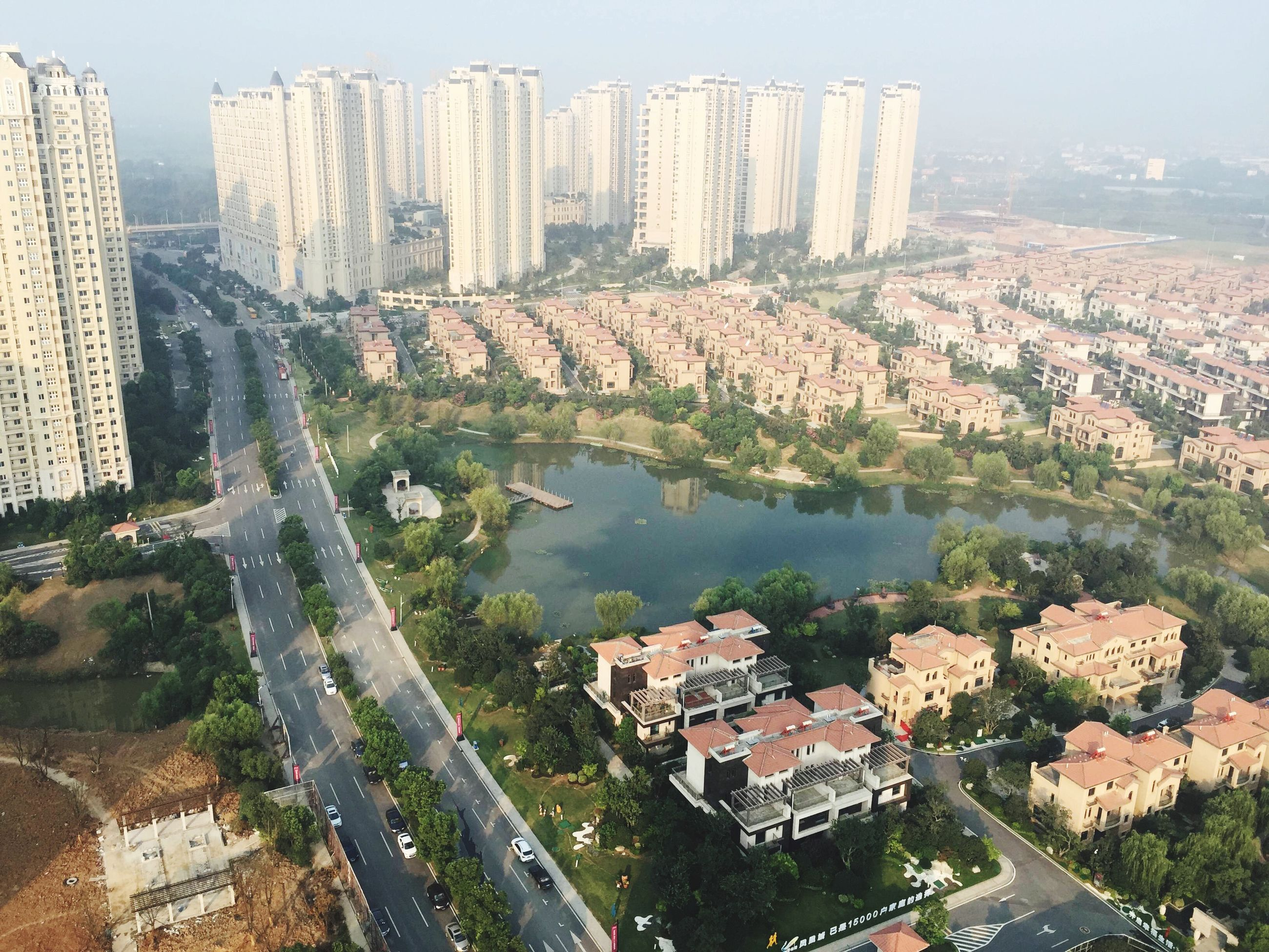 building exterior, architecture, built structure, city, cityscape, water, residential district, high angle view, residential structure, residential building, crowded, river, house, town, tree, clear sky, townscape, day, outdoors, no people