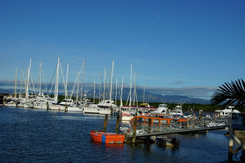 Boats moored in calm sea against blue sky