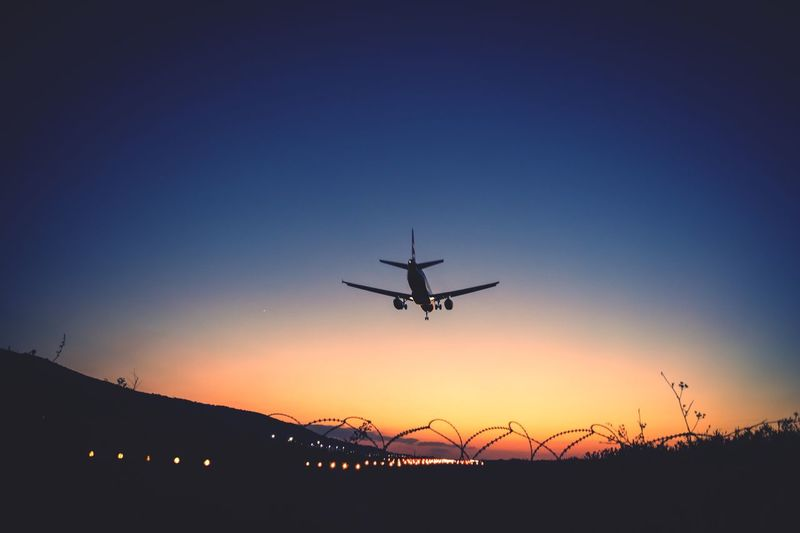 Low angle view of silhouette airplane against clear sky during sunset