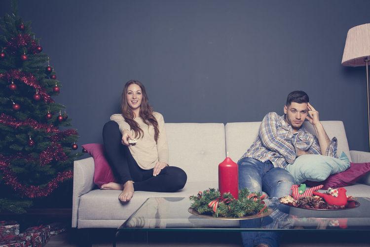 Man and woman sitting on sofa during christmas