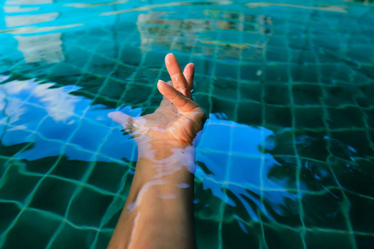 Midsection of person swimming in pool
