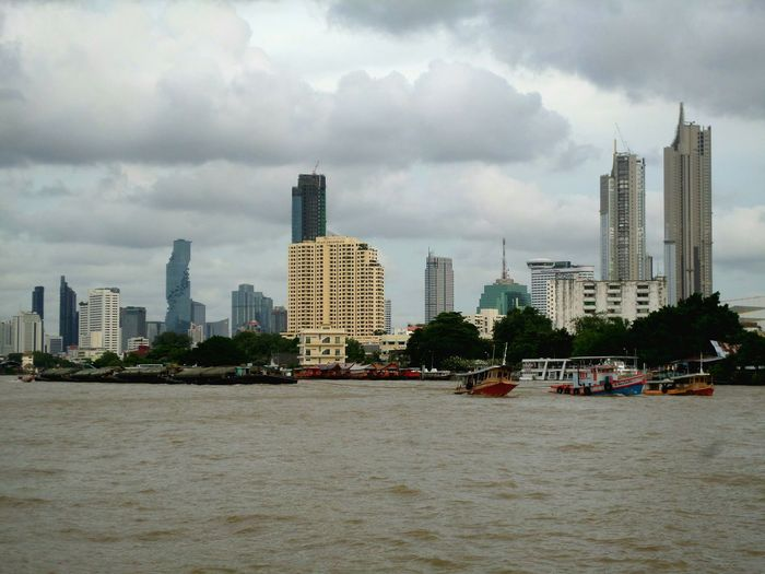 Sea by modern buildings against sky in city