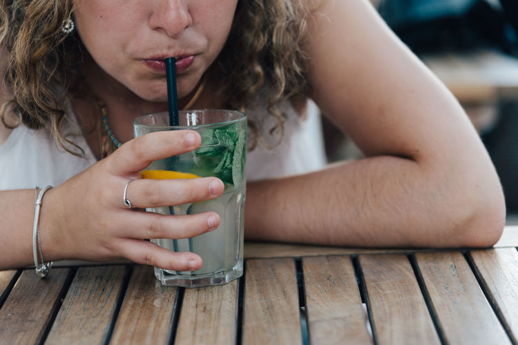 Midsection of woman having drink while sitting at table