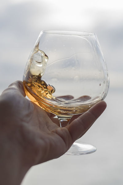 Snifter brandy swirl portrait Adult Adults Only Alcohol Beach House Beverage Brandy Close-up Day Dram Drink Holding Human Body Part Human Hand One Man Only One Person Only Men Outdoors People Refreshment Sky Snifter Whiskey