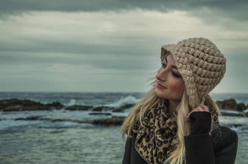 Portrait Of Woman By Sea Against Sky During Winter