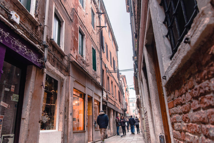venice italy gondola boats on channel between buildings Building Exterior Architecture Built Structure City Building Group Of People Men Incidental People Street Day Residential District Women Lifestyles Real People People Walking Adult Alley Low Angle View Outdoors